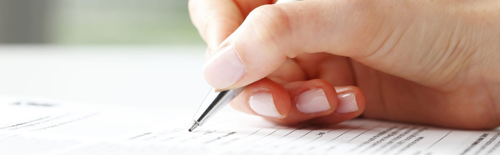 person holding pen to paper