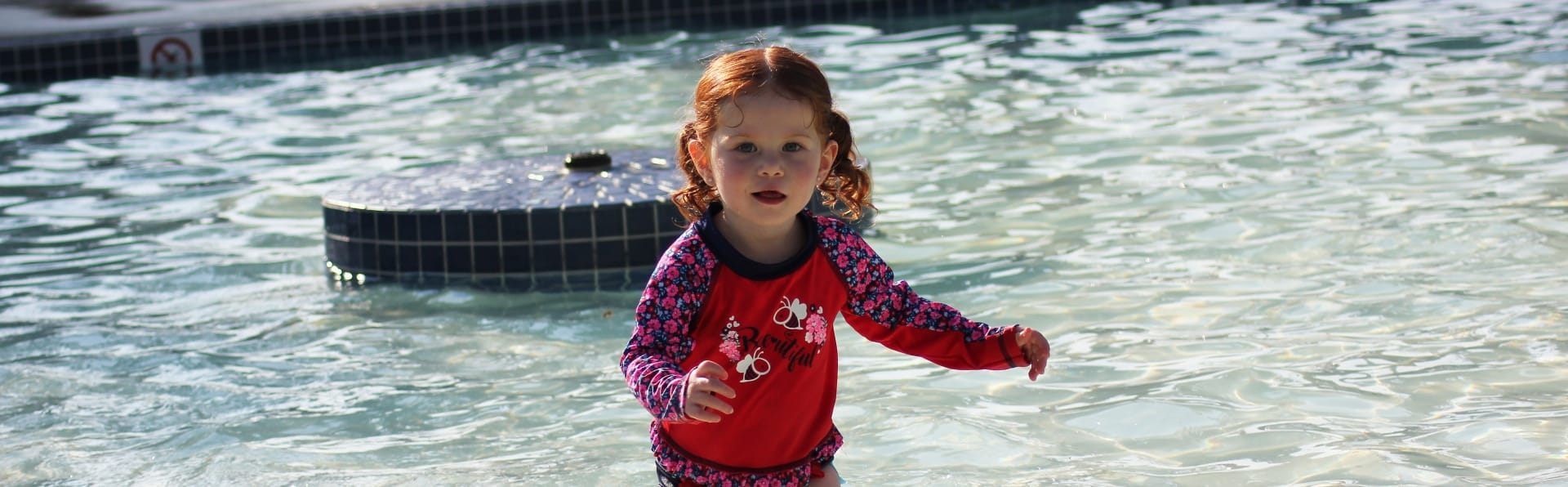 Little girl playing in water at the spray park.
